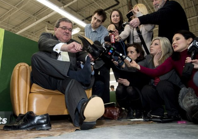 Finance Minister Jim Flaherty puts on his annual pre-budget shoes at the Roots Leather Factory in Toronto on Wednesday, March 20, 2013. THE CANADIAN PRESS/Nathan Denette