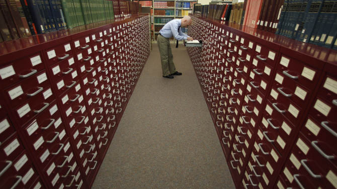In this Wednesday, Aug. 24, 2011 photo, Peter Sokolowski, editor at large for Merriam-Webster Inc., thumbs through the index card files at the dictionary publisher's headquarters in Springfield, Mass. More than 100 new terms are being revealed Thursday for the dictionary publisher's newest edition. (AP Photo/Charles Krupa)