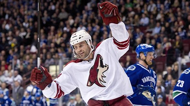 Kyle Chipchura #24 of the Phoenix Coyotes celebrates after scoring an empty net goal while Henrik Sedin #33 of the Vancouver Canucks looks on