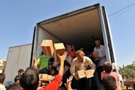 Syrian residents take goods from a truck which rebels captured at the Bab al-Hawa border crossing with Turkey on July 20. Dozens of Turkish truck drivers on Saturday accused rebel fighters of the Free Syrian Army of having burned and looted their lorries as they stormed a border post in Syria