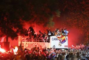 Real Madrid players celebrate on top of an open bus as they arrive at the Cibeles square in Madrid
