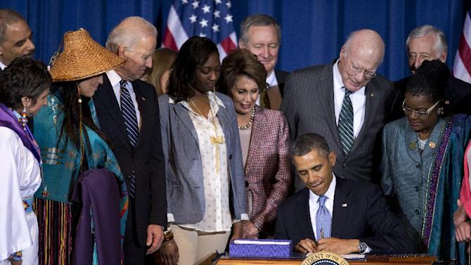 President Barack Obama, joined by Vice President Joe Biden, Senate Patrick Leahy, D-Vt., House Minority Whip Steny Hoyer of Md., members of women's organizations, law enforcement officials, tribal leaders, survivors, advocates and members of Congress, signs the Violence Against Women Act, Thursday, March 7, 2013, during a ceremony at the Interior Department in Washington.  (AP Photo/Manuel Balce Ceneta)