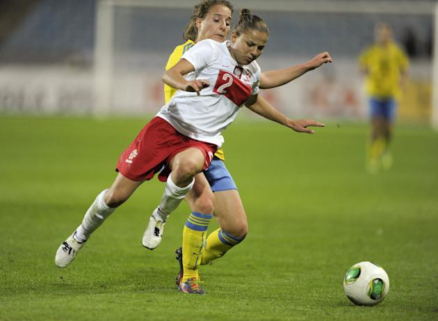 Poland's Aleksandra Sikora, front, fights for the ball with Sweden's Antonia Gransson, during the ladies' football World Championships qualification match at Swedbank Stadium in Malmo, Sweden, Saturda