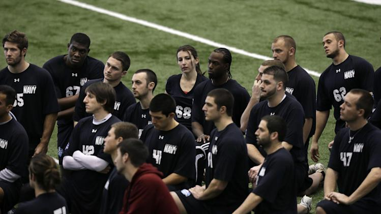 Lauren Silberman, top center, kneels on the indoor turf before kicker tryouts at the NFL football regional combine workout on Sunday, March 3, 2013, in Florham Park, N. J.(AP Photo/Mel Evans)