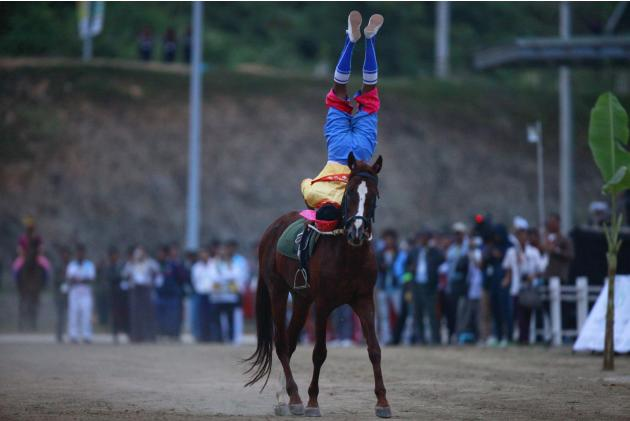 A rider in traditional dress performs with a horse during the opening ceremony of the Equestrian competition at the 27th SEA Games in Naypyitaw