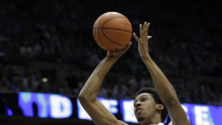 North Carolina's Desmond Hubert (14) shoots as Duke's Josh Hairston (15) defends during the first half of an NCAA college basketball game in Chapel Hill, N.C., Saturday, March 9, 2013. (AP Photo/Gerry Broome)