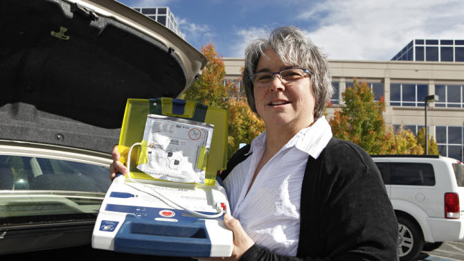 "In this Tuesday, Oct. 23, 2012 photo, Mary Tappe holds up the defibrillator that she keeps in the trunk of her automobile during a work break at the Western Union headquarters in Englewood, Colo. Tappe owes her life to bystanders' willingness to offer help. In 2004, she collapsed at her office in Iowa. A co-worker called 911; another quickly began CPR and someone else used the office's automated heart defibrillator. An ambulance took Tappe to the hospital, where doctors said her heart had stopped. They never determined why but implanted an internal defibrillator. Tappe, 51, who now lives in Englewood, Colo., said raising awareness about the importance of CPR is ""incredibly important because that's the first step"" to helping people survive. (AP Photo/Ed Andrieski)"
