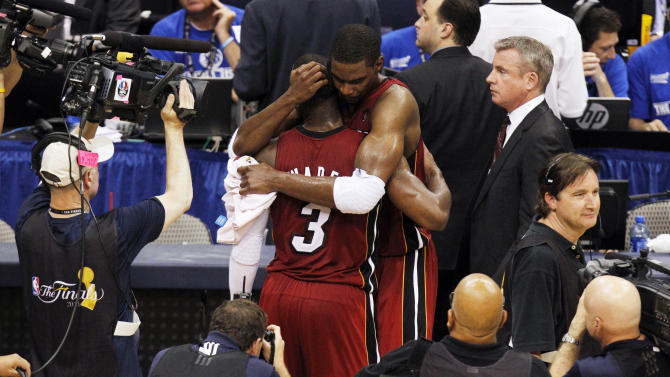 Miami Heat's Dwyane Wade (3) hugs Chris Bosh after the second half of Game 3 of the NBA Finals basketball game against the Dallas Mavericks Sunday, June 5, 2011, in Dallas. The Heat won 88-86 take a 2-1 lead in the series. (AP Photo/LM Otero)