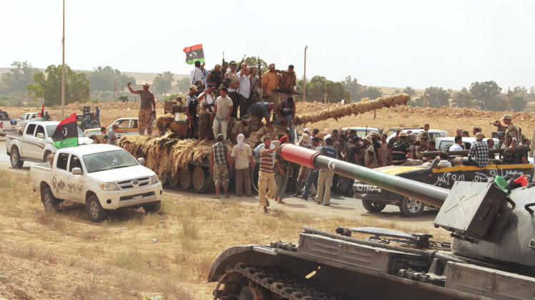 Revolutionary fighters celebrate the capture of a tank, draped in sheepskins as camouflage, from pro-Gadhafi resistance forces in Sirte, Libya, Tuesday, Sept.20, 2011. Revolutionary fighters have not been able to take over central positions in Sirte. Pro-Gadhafi forces have the advantage of knowing the city and are heavily armed, making it impossible for the former rebels to stand in at night after advancing during the day. (AP Photo/Gaia Anderson)