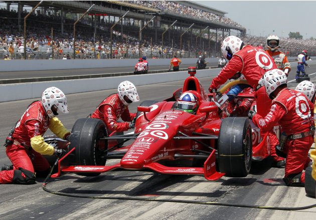 Crew members for Dario Franchitti, of Scotland, service the car in a pit stop during IndyCar's Indianapolis 500 auto race at Indianapolis Motor Speedway in Indianapolis, Sunday, May 27, 2012. (AP Phot