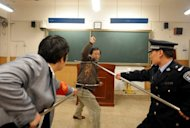 Chinese policemen show teachers and school workers how to defend themselves during an attack at a Beijing school in 2010. Three children have been killed and more than a dozen injured in an axe attack at a primary school in southern China, state media says