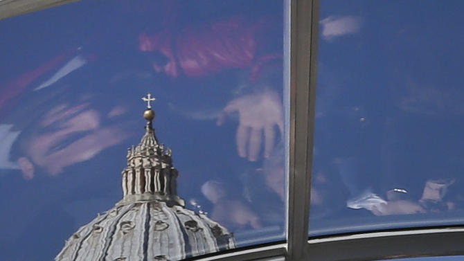 """Faithful are reflected in the roof of Pope Benedict XVI's pope-mobile as he arrives to celebrate his last general audience in St. Peter's Square, at the Vatican, Wednesday, Feb. 27, 2013. Benedict XVI basked in an emotional sendoff Wednesday at his final general audience in St. Peter's Square, recalling moments of """"joy and light"""" during his papacy but also times of great difficulty. He also thanked his flock for respecting his decision to retire. (AP Photo/Alessandra Tarantino)"""