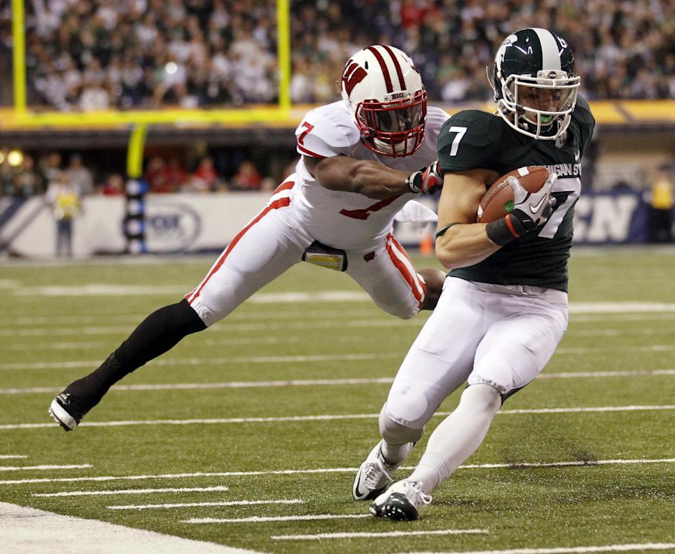 Michigan State's Keith Nichol avoids the tackle of Wisconsin's Aaron Henry during the first half of the Big Ten conference championship NCAA college football game on Saturday, Dec. 3, 2011, in Indianapolis. (AP Photo/Michael Conroy)