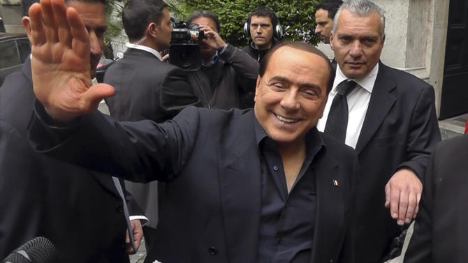 In this frame made from video footage made available by APTN, former Premier Silvio Berlusconi waves to supporters outside his residence, in Rome, Saturday, April 27, 2013. Berlusconi says he thinks Italy will finally get a government Saturday, a broad coalition that brings his conservatives back in power. The media mogul also told journalists in Rome Saturday he wouldn't be part of the Cabinet headed by a center-left leader Enrico Letta. (AP Photo/via APTN)