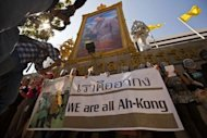 Thai activists wear masks representing imprisoned Ampon Tangnoppakul, alias Ah-Kong, while protesting under a portrait of Thai King Bhumibol Adulayadej outside the criminal court in Bangkok in 2011. In May Ah Kong, a 62-year-old grandfather, died in custody while serving a 20-year sentence for allegedly sending text messages that were deemed insulting to the royal family