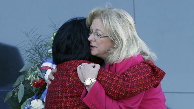 Sandra Anderson, left, widow of astronaut Michael P.Anderson, and Evelyn Husband-Thompson, widow of Colonel Rick Husband, space shuttle Columbia commander, embrace in front of a memorial wreath during a remembrance ceremony on the 10th anniversary of the loss of space shuttle Columbia crew at the Kennedy Space Center Visitor Complex,  Friday, Feb. 1, 2013, in Cape Canaveral, Fla. (AP Photo/John Raoux)