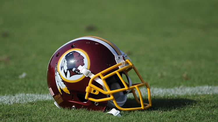 """A Washington Redskins football helmet lies on the field during NFL football minicamp, Wednesday, June 18, 2014, in Ashburn, Va. The U.S. Patent Office ruled Wednesday, June 18, 2014, that the Washington Redskins nickname is """"disparaging of Native Americans"""" and that the team's federal trademarks for the name must be canceled. The ruling comes after a campaign to change the name has gained momentum over the past year"""