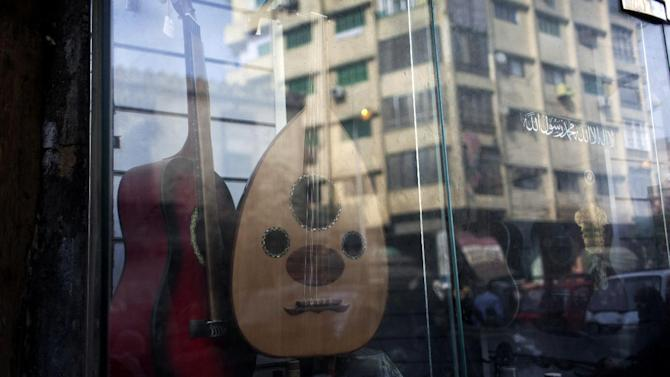 "In this Thursday, Jan. 3, 2013 photo, modern buildings are reflected on the glass of an instrument shop with an Arabic sticker that reads, ""there is no God but God and Muhammad is his prophet,"" on Mohammed Ali street, a street modeled after Paris' boulevards and home to musicians, belly-dancers and instrument makers, in downtown Cairo, Egypt. The shops making, repairing and selling musical instruments that once packed the street are disappearing, along with their window displays of lute-like, stringed ouds, qanouns  and tablas -- a drum made equally for the rapid-fire hand beats of belly-dance tunes or for the languid rhythms of a love ballad by Umm Kalthoum, the most famed singer of classical Arabic music. (AP Photo/Nasser Nasser)"