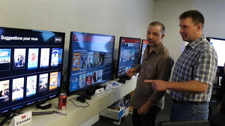 "In this photo taken Wednesday, July 10, 2013, Chris Jaffee, Netflix VP of Product Innovation, left, and Bob Heldt, Director of Engineering, look over video displays as they await the debut of ""Orange is the new black"" in Los Gatos, Calif. (AP Photo/Michael Liedtke)"