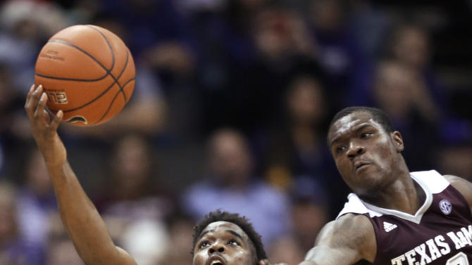 Kansas State forward Nino Williams (11) catches an inbound pass while covered by Texas A&M guard Jalen Jones (12) during the second half of an NCAA college basketball game in Kansas City, Mo., Saturday, Dec. 20, 2014. Kansas State defeated Texas A&M 71-64. (AP Photo/Orlin Wagner)