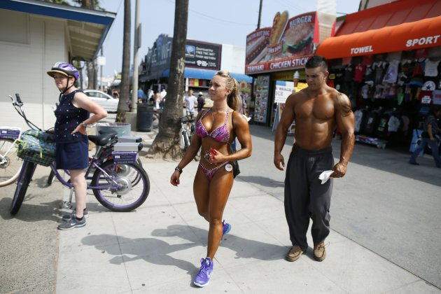 A couple arrives to compete in the Muscle Beach Independence Day bodybuilding contest on Venice Beach in Los Angeles, California