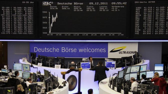 File photo of traders working at their desks in front of the DAX board and banner reading 'Deutsche Boerse Welcomes Ultrasonic' at the Frankfurt stock exchange