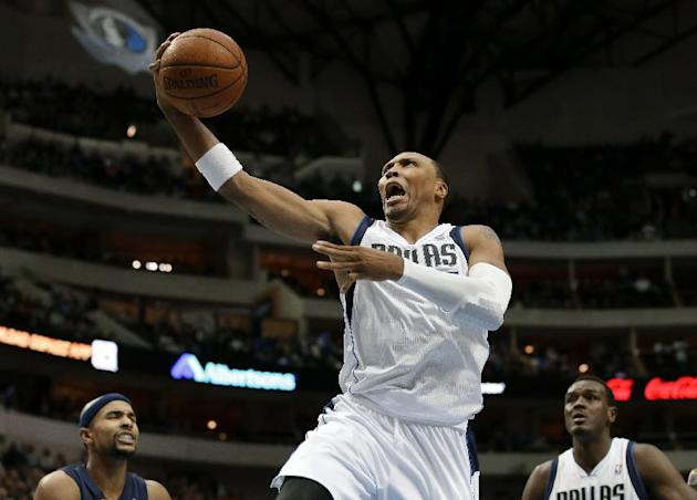 Dallas Mavericks' Shawn Marion, center, leaps to the basket for a shot attempt as Memphis Grizzlies' Jerryd Bayless, left, and the Mavericks Samuel Dalembert, right, watch in the second half of an NBA