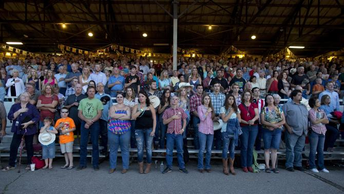 The crowd stands for the national anthem before the start of the Prescott Frontier Days rodeo, Wednesday, July 3, 2013 in Prescott, Ariz. A mile-high city about 90 miles northwest of Phoenix, Prescott remains a modern-day outpost of the pioneer spirit. It's that spirit that will guide officials as they navigate the days ahead and figure out how to honor the elite Hotshot firefighters who died in a nearby wind-driven wildfire that is still burning. (AP Photo/Julie Jacobson)