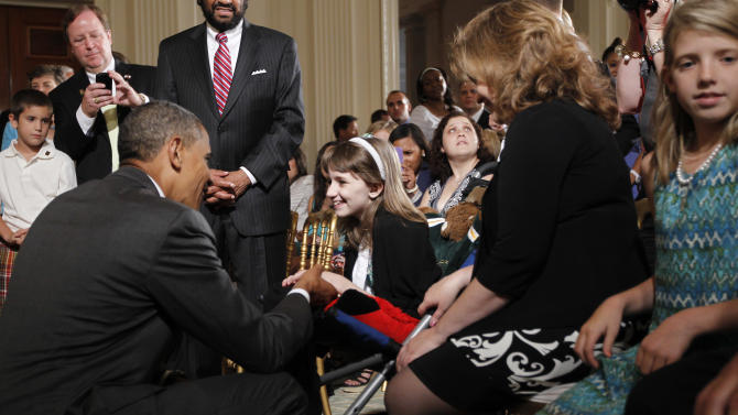 President Barack Obama, left, stops to greet Haley Klepper, 10, center, during a ceremony for the 2012 NCAA Women's basketball champions Baylor University Bears in the East Room of the White House in Washington, Wednesday, July 18, 2012. Also seated in the front row are Haley's mother, Brenda Klepper, and sister Hannah Klepper, 12, far right, from Waco Texas. (AP Photo/Pablo Martinez Monsivais)