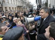 Newly elected Ukrainian interior minister Arsen Avakov (R) holds a loud-speaker as he addresses anti-government protesters outside the Ukrainian parliament building in Kiev February 22, 2014. REUTERS/Vasily Fedosenko