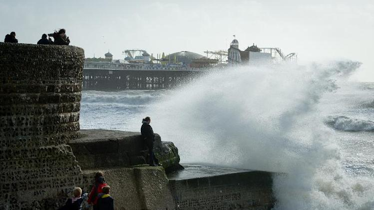 Large waves break against barriers on the seafront in Brighton, southern England on October 27, 2013 as a predicted storm starts to build