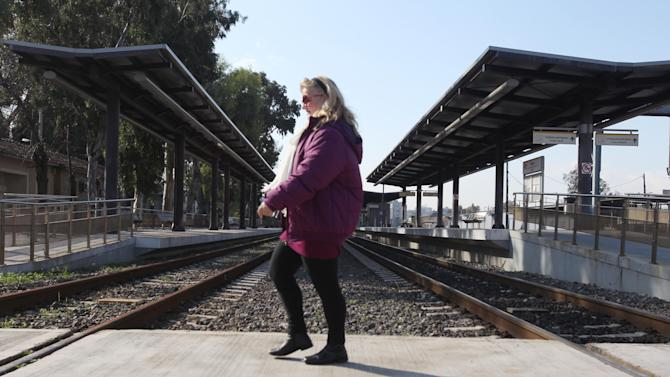 A pedestrian passes an empty railway station during a strike in Athens, Monday, Jan. 28, 2013. Employees of Greece's railway have joined strikes by other public transport workers to protest pay cuts and the cancellation of their existing pay salary agreements, as part of the country's austerity measures and bailout commitments. (AP Photo/Thanassis Stavrakis)