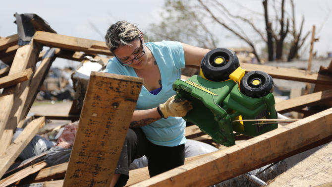 LaTisha Garcia finds her son's favorite truck as she digs through the rubble of her tornado demolished home following Monday's tornado in Moore, Okla., Thursday, May 23, 2013. Garcia carried her injured daughter away from a school that was hit by a tornado on Monday. (AP Photo/Sue Ogrocki)