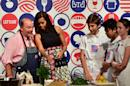 US First Lady Michelle Obama (2ndL) listens to Chef Mario Batali as she cooks with youth from the American School of Milan at the James Beard American Restaurant during a visit in Milan on June 17, 2015