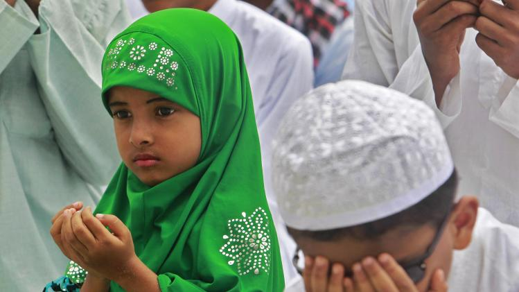Muslim children offer prayers during Eid al-Fitr at a mosque in Agartala