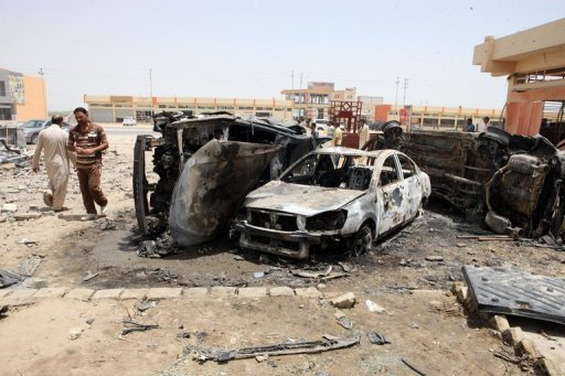 Iraqi men walk past the bombed remains of vehicles in Khaldiya, 10 km east of Ramadi, in June 2012. A suicide bomber blew up a car packed with explosives near an anti-Qaeda militiaman's home in western Iraq on Friday, killing six people, the latest victims of a spike in nationwide unrest