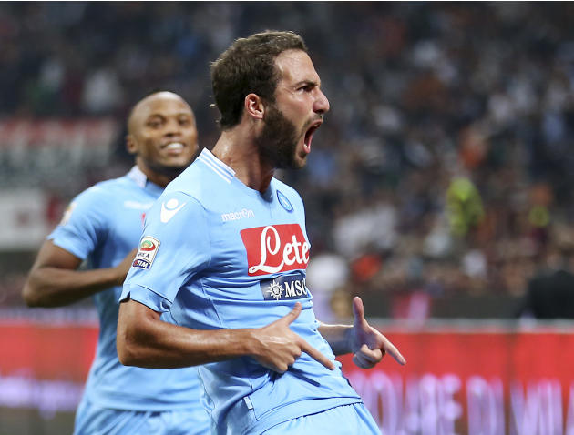 Napoli forward Gonzalo Higuain, right, of Argentina, celebrates after scoring his side's second goal during the Serie A soccer match between AC Milan and Napoli at the San Siro stadium in Milan, Italy