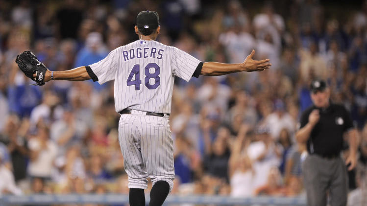 Colorado Rockies starting pitcher Esmil Rogers reacts toward third base umpire Bob Davidson, right, after being called for a balk with the bases loaded during the seventh inning of their baseball game against the Los Angeles Dodgers, Friday, Aug. 26, 2011, in Los Angeles. (AP Photo/Mark J. Terrill)