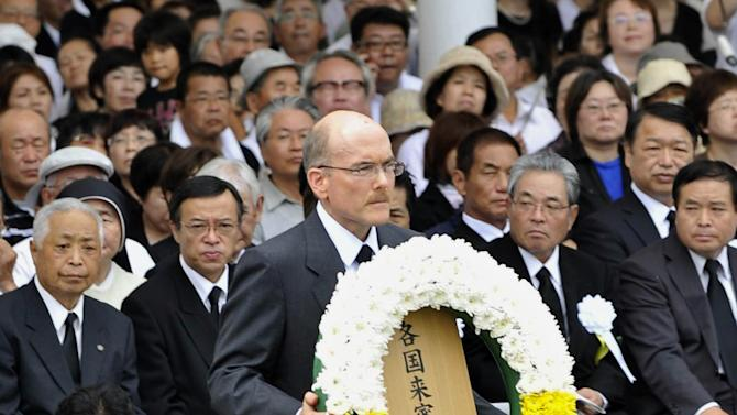 James Zumwalt, deputy chief of mission at the U.S. Embassy in Tokyo, carries a wreath to the altar set up in Nagasaki Peace Park in Nagasaki, southern Japan Tuesday, Aug. 9, 2011. The U.S. has sent its first representative to the annual memorial for the atomic bombing of Nagasaki, as the Japanese city remembered the historic horrors of radiation amid the nation's unfolding nuclear crisis. (AP Photo/Kyodo News) JAPAN OUT, MANDATORY CREDIT, NO LICENSING IN CHINA, FRANCE, HONG KONG, JAPAN AND SOUTH KOREA