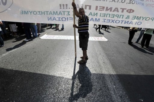 &lt;p&gt;A striking municipal worker holds a banner in Athens. Anti-austerity protests clogged the city as the government struggled to finalize additional cutbacks with its creditors and sought to jumpstart a privatization drive delayed for months.&lt;/p&gt;