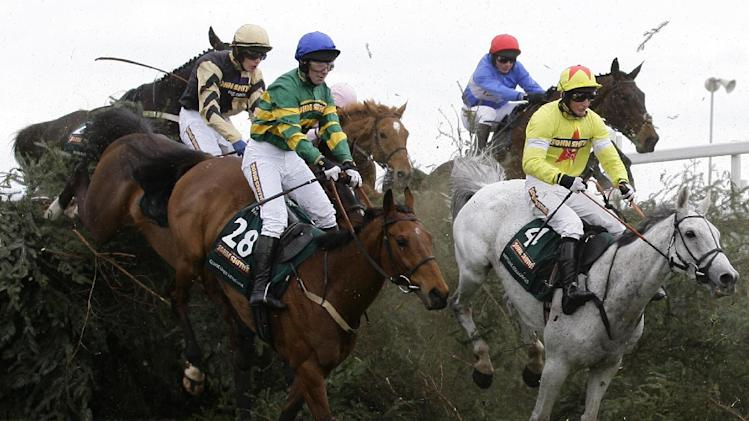 Neptune Collonges, right, with Jockey Daryl Jacob onboard jumps The Chair on the way to winning the Grand National horse race after a photo finish with SunnyHillBoy at Aintree Racecourse Liverpool, England, Saturday, April 14, 2012. (AP Photo/Jon Super)