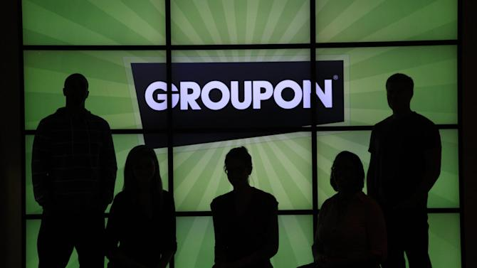 "In this Thursday, Sept. 22, 2011, photo, employees at Groupon pose in silhouette by the company logo in the lobby of the online coupon company's Chicago offices.  Groupon Inc., the No. 1 online deals service, failed to show investors on Thursda, Nov. 8, 2012, that its business is growing as quickly as they would like, as it was hurt by what it called ""continued challenges"" from the economic weakness in Europe. (AP Photo/Charles Rex Arbogast)"