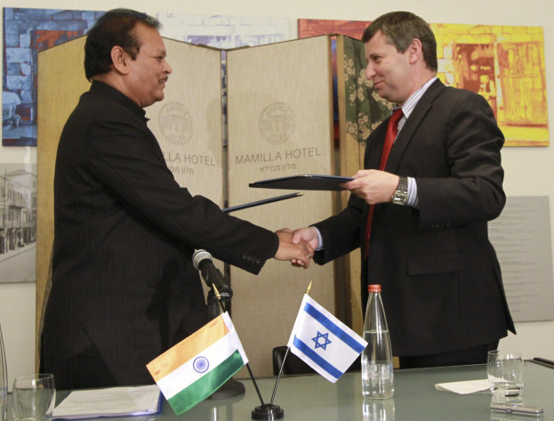 Israel's Tourism Minister Stas Misezhnikov, right, shakes hands with his Indian counterpart Subodh Kant Sahai, left, during a media briefing in Jerusalem, Sunday, June 24, 2012. In the meeting Sunday Misezhnikov announced Israel will train more Hindi-speaking guides and build 200,000 new hotel rooms to welcome the anticipated deluge of tourists. Misezhnikov and Sahai signed a formal working agreement to encourage travel between their two countries. (AP Photo/Blake Sobczak)