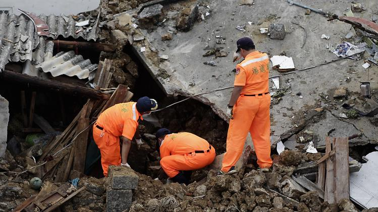 Rescue personnel survey the wreckage of a TransAsia Airways turboprop plane that crashed, on Penghu island