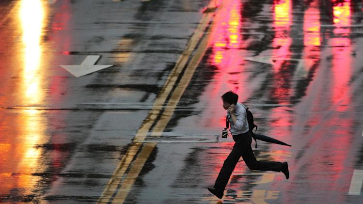 A man runs to make the crossing light through strong winds and rain from approaching Typhoon Matmo in Taipei, Taiwan, Tuesday, July 22, 2014. The eye of Typhoon Matmo is expected to make landfall in eastern Taiwan early Wednesday bringing heavy rains and winds with gusts over 130 kilometers (85 miles) per hour. (AP Photo/Wally Santana)