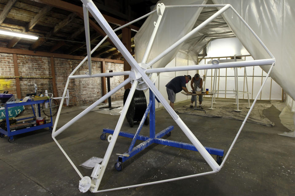 In this photo taken  Thursday, June 21, 2012, workers repaint a section of a Vollis Simpson whirligig at a warehouse where renovations are taking place in Wilson, N.C., Thursday, June 21, 2012. (AP Photo/Gerry Broome)