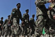 Afghan soldiers take part in a handover ceremony after the United States formally handed control to Afghanistan of more than 3,000 detainees at the controversial Bagram prison, but disagreements remain over the fate of hundreds of inmates