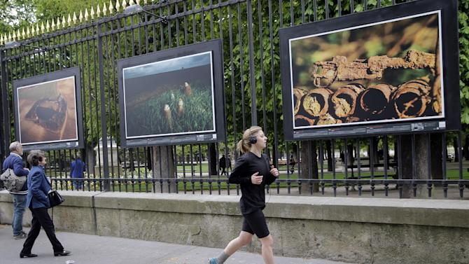 """A woman runs next to """" """"A rusting rifle"""" a picture by British photographer Michael St Maur Sheil at the Paris Luxembourg gardens, Tuesday, April 8, 2014 as part of an exhibition """" Fields of Battle - Lands of Peace 14-18 """". Captured over a period of seven years, Michael's photography combines a passion for history and landscape and presents a unique reflection on the transformation of the battlefields of the Great War into the landscape of modern Europe. (AP Photo/Christophe Ena)"""