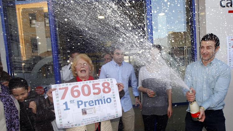Workers and friends of a lottery office celebrate. after selling a ticket with the number 76058 corresponding to the Jackpot worth euro 4 million or euro 400,000  for each tenth of the ticket, during the Spanish National Lottery draw,  in Manises, Valencia, eastern Spain,  Saturday Dec. 22, 2012 After a brutal year of economic hardship that deepened with unemployment hitting 25 percent, Spaniards across the country Saturday were hoping for relief from payouts by the nation's famed Christmas lottery _ the world's richest, with €2.5 billion ($3.3 billion) in tax-free awards.  (AP Photo/Alberto Saiz)