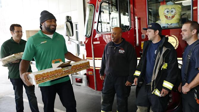 """IMAGE DISTRIBUTED FOR SUBWAY - Jared """"The SUBWAY Guy"""", left and New England linebacker Jerod Mayo, right, surprise Boston Fire Department with Giant Sub as part of SUBWAY Customer Appreciation Month on Tuesday, Dec. 11, 2012 in Boston. (Photo by Bizuayehu Tesfaye/Invision for SUBWAY/AP Images)"""